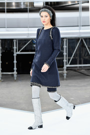 Silver knee-high boots with black toe caps and heels completed Bella Hadid's look.