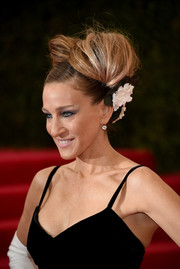 Sarah Jessica Parker was elaborately coiffed with flower-adorned victory rolls during the Met Gala.