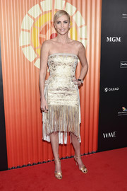 Charlize Theron looked radiant in a strapless gold dress with a fringed hem at the Africa Outreach Project fundraiser.