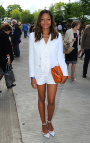 Naomie Harris accessorized with an orange leather clutch by Marni for a splash of color to her white outfit.