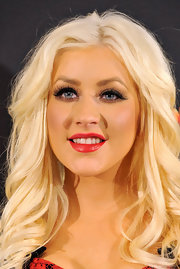 Christina Aguilera gave her bold lashes a sultry touch with satin red lipstick. A wispy cat eye rounded out her retro look.