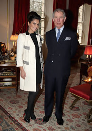 Cheryl dons a white wool coat with black accents while posing with Prince Charles.