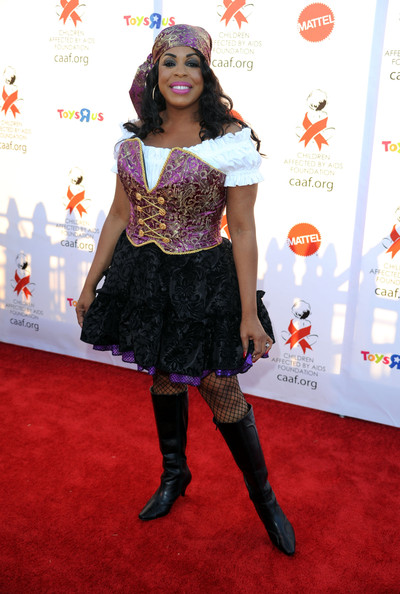 Niecy dons black knee-high boots for her Halloween costume.