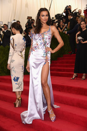 Irina Shayk flaunted some leg in a one-sleeve lavender gown by Atelier Versace, featuring an embroidered bodice and an up-to-the-hip slit, during the Met Gala.
