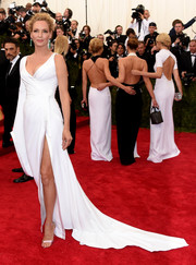 Uma Thurman was an ageless beauty in an asymmetrical white wrap gown by Atelier Versace at the Met Gala.