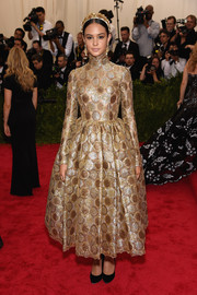 Courtney Eaton looked radiant in a high-neck, ballerina-length gold dress by Dolce & Gabbana at the Met Gala.