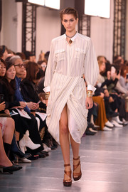 Kaia Gerber looked smart in a striped shirtdress with a crossover tulip skirt while walking the Chloe runway.