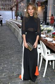 Chrissy Teigen looked sultry yet elegant in a sheer black blouse during the Belgian National Day celebration.