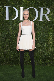 Cara Delevingne went for an edgy-sexy finish with a pair of black thigh-high boots, also by Dior.