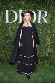 Eva Herzigova channeled her inner saloon girl in a black Dior corset gown with white trim during the label's '70 Years of Creation' exhibition.