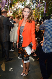 Olivia Palermo sported a multi-patterned ensemble at the Christian Dior fashion show, consisting of a black-and-white printed clutch, a lace skirt, and a houndstooth bustier.