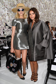 Miroslava Duma was almost drowning in her oversized silver Dior coat during the label's fashion show.