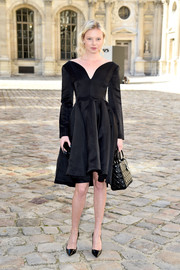 Dasha Zharova looked tres elegant at the Christian Dior fashion show in a long-sleeve LBD with a curvy V neckline.