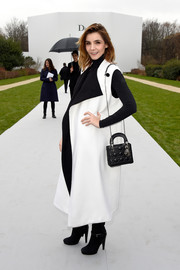 Clotilde Courau cut a stylish figure in a sleeveless black-and-white coat layered over a turtleneck during the Dior Couture show.