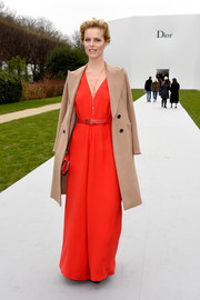Eva Herzigova layered a beige wool coat over her jumpsuit, taming the bright red with a spot of neutral.