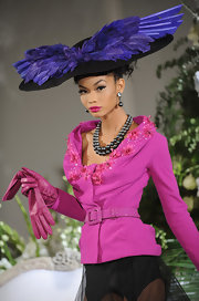 Chanel looks electrifying. She is wearing a black oversized hat with blue-purple feathers. It is derby ready,beautiful, and one of a kind. The hat works with her embellished magenta jacket