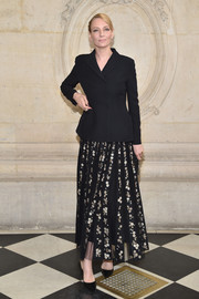 Uma Thurman layered a black jacket over a floral dress, both by Dior, for the label's fashion show.