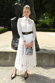 Karlie Kloss cut a stylish figure in a white lace shirtdress by Dior during the brand's Couture Fall 2018 show.
