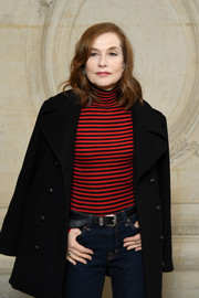 Isabelle Huppert looked youthful in a fitted red and black turtleneck by Dior while attending the brand's Fall 2018 show.