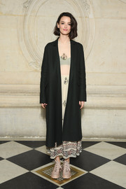 Charlotte Le Bon layered a black Dior coat over a nude print dress for the brand's Fall 2019 show.