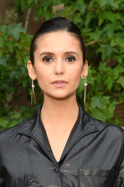 Nina Dobrev styled her hair into a side-parted bun for the Dior Spring 2020 show.