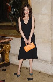 Olga Kurylenko injected an extra pop of color with a quilted orange purse by Dior.