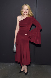 Patricia Clarkson worked a maroon one-sleeve dress with a fluted cuff at the Christian Siriano fashion show.