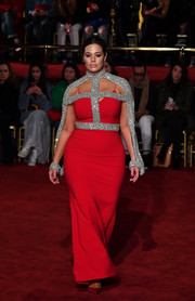 Ashley Graham looked quite the glamazon in a curve-hugging red slip gown with crystal harness detailing at the Christian Siriano runway show.