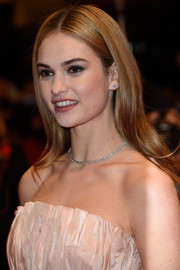 Lily James complemented her strapless dress with a delicate diamond tennis necklace by De Beers.