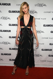 Going Alexander McQueen all the way, Karlie Kloss accessorized with a crescent-shaped brass clutch.