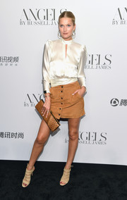 For her bag, Toni Garrn chose a printed tan clutch.