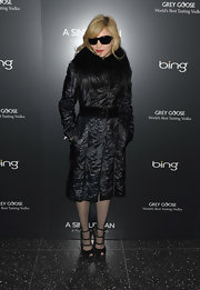 Madonna looked very Anna Wintour in her black fur embellished coat. She topped her sophisticated look off with a pair of ankle strap peep-toes.