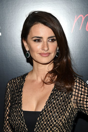 Penelope Cruz added more glamour with a pair of dangling emerald earrings by Chopard.