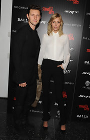 Black skinny pants with ruffled bottoms added a subtle feminine touch to Anja Rubik's androgynous look.