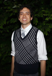 Geoffrey shows off his chic preppy side with this plaid sweater vest paired with jeans and white button-up.