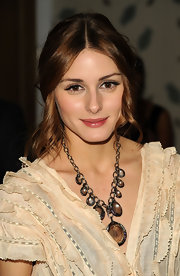 Olivia Palermo accented her V-neck silhouette with a gemstone neckalce.