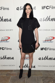 For her purse, Krysten Ritter chose a black croc-embossed envelope clutch.