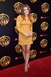 Isla Fisher went ultra girly in a smocked mustard mini dress by Ulla Johnson at CinemaCon 2018.