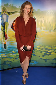 Eva Herzigova added glamor to her stunning draped dress with a black satin clutch with a bejeweled clasp.