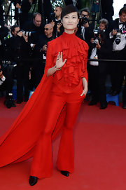Li Yuchun rocked a totally bold look with this red ruffled blouse that featured a cape detail.