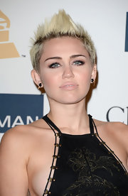 Miley Cyrus chose her signature fauxhawk with super-high center spike while attending a pre-Grammy gala.