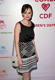 Alexis Bledel teamed her black-and-white benefit look with a Kristin Embossed Python Crossbody bag.