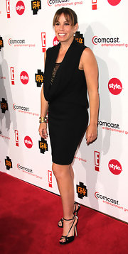 Melissa wears a little black dress with a deep cowl neck.