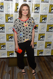 Emily Deschanel accessorized with a faceted clutch in an eye-popping shade of orange.