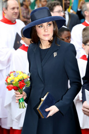 Kate Middleton went for a monochromatic look, consisting of a Jimmy Choo suede clutch, a wool coat, and a wide-brimmed hat, at the Commonwealth Day service.