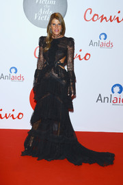 Anna dello Russo went for goth glamour in a tiered black lace cutout gown by Roberto Cavalli at the Convivio 2016 photocall.