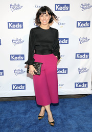 Constance Zimmer styled her outfit with a pair of gold and black striped pumps.