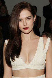 Zoey Deutch attended the Cushnie et Ochs fashion show wearing her long hair loose with a deep side part.