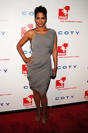 "Halle paired her gorgeous side-swept gray dress with the shimmering gunmetal gray ""Metal Carbon Sandals""."