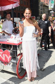 Chrissy Teigen looked like a modern flapper girl in a white strapless top with a fringed hem during the launch of the new DKNY fragrance.